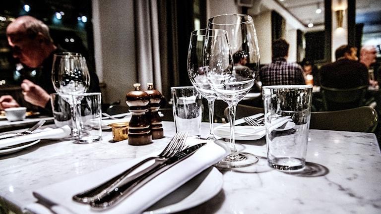Bestick och glas på ett bord på en restaurang.