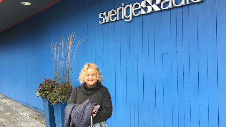 Kvinna står framför blå vägg med Sveriges Radio-logga