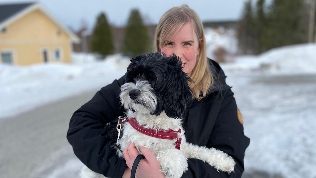 Blond kvinna i svart jacka som lyfter upp en svartvit hund i famnen.