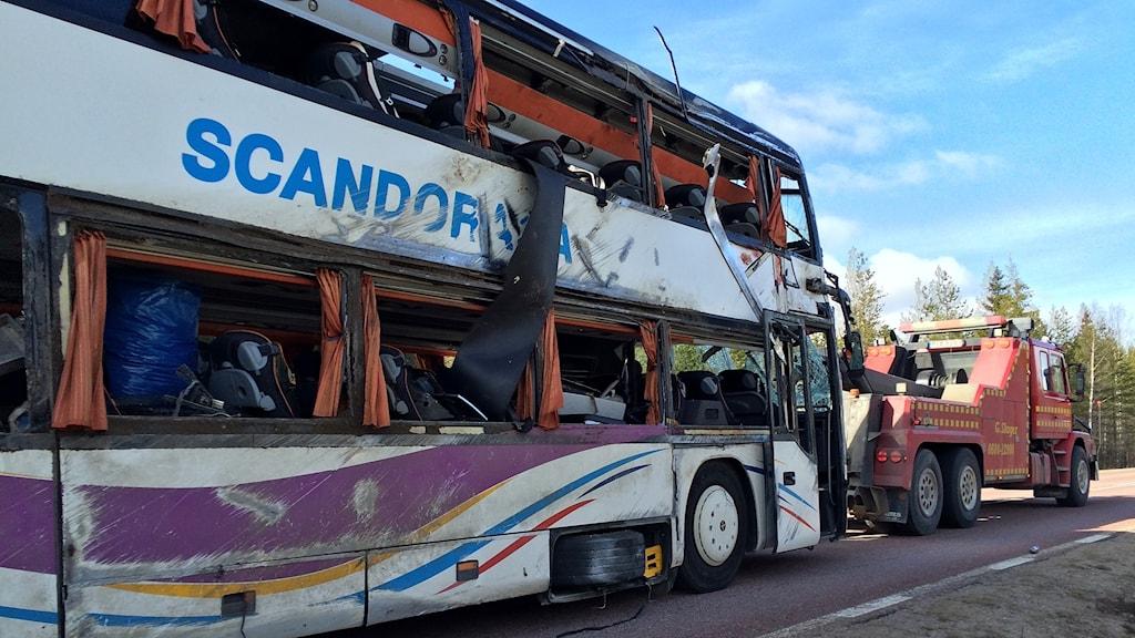 Buss som kört av vägen bärgas av bilbärgare.
