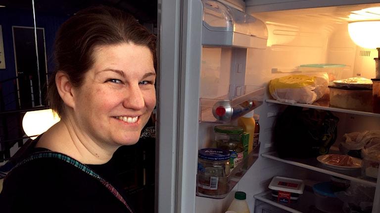 Kvinna står framför öppet kylskåp.