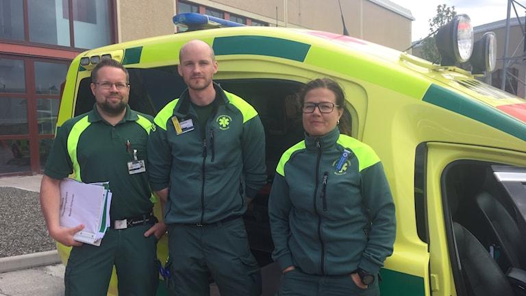 Tre personer i uniform står framför ambulansfordon.