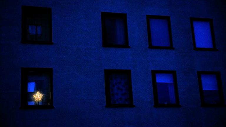 Mörk husfasad, ett fönster är upplyst av en elektrisk julstjärna.