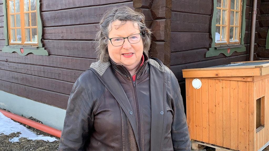 Kvinna med mörk jacka och grått lockigt hår som står framför en stuga.