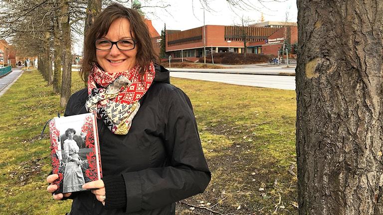 kvinna med svart jacka stående i trädallé med en bok i famnen