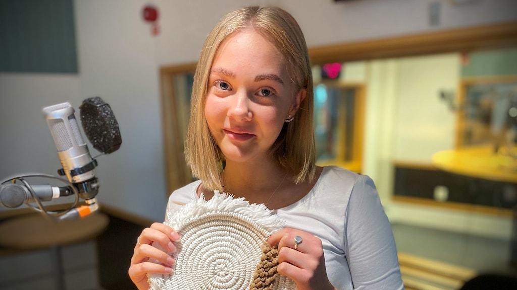 En tjej i kort blond hår står i en radiostudio med ett hantverk gjort i ljust garn i handen.