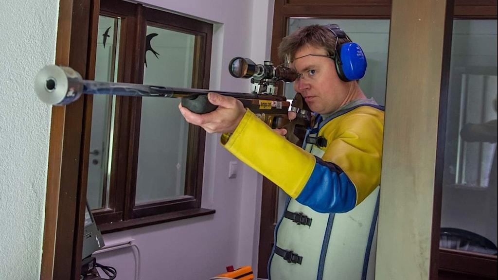 Bild på en mörkhårig man som har ett gevär i handen.