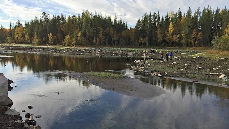 Människor vandrar längs en å