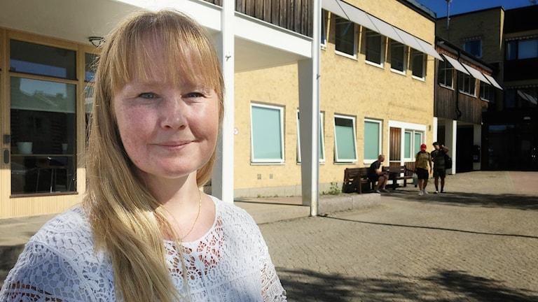 Kvinna i vit spetsblus framför kommunhuset Strömsund