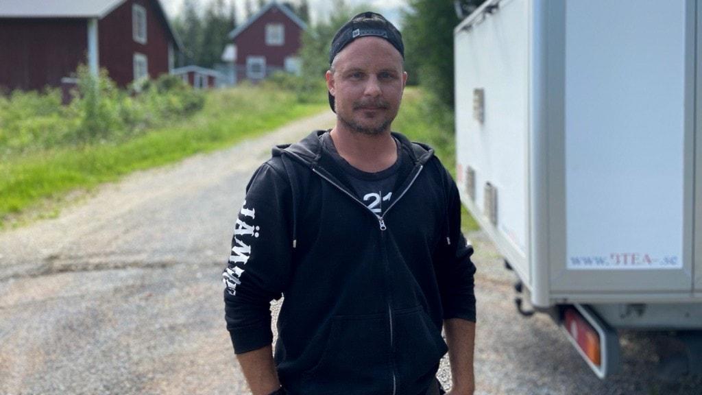 En man i svart munktröja står framför en vit skåpbil.