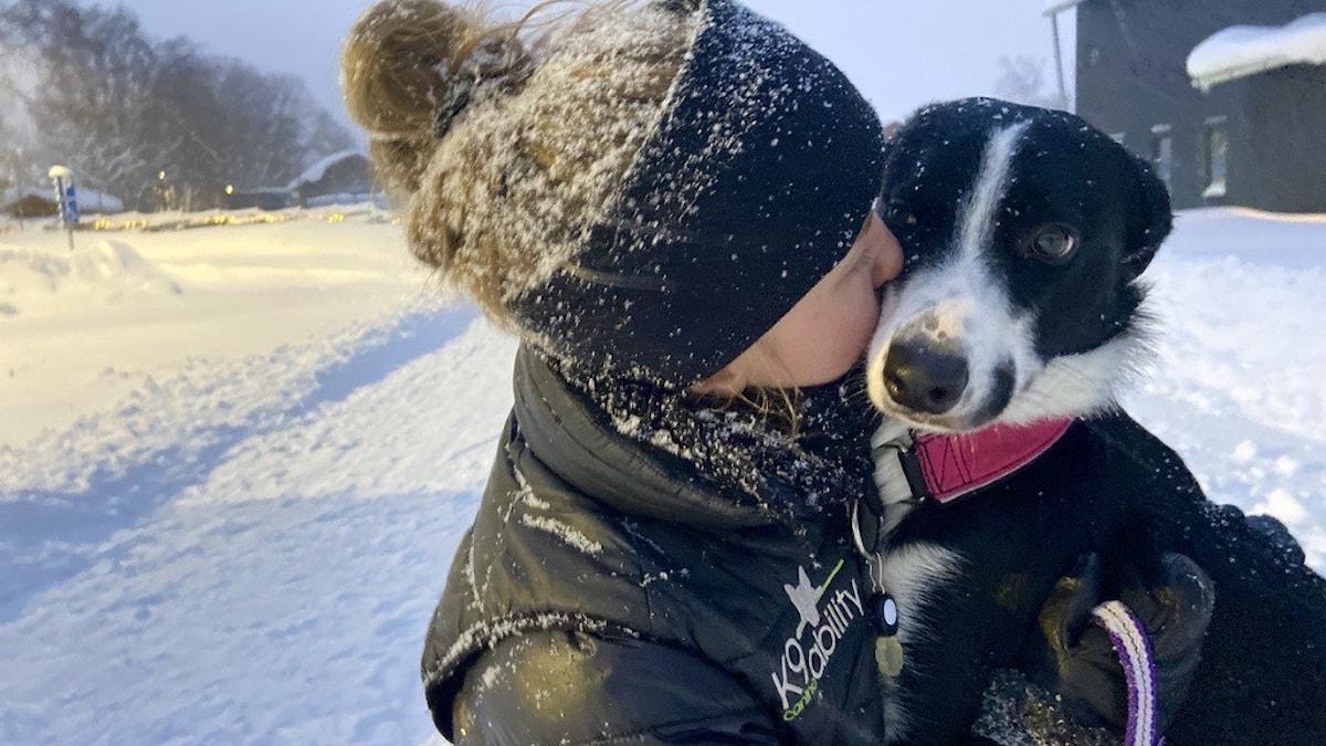 Kvinna i svart pannband som kramar sin svart/vita hund.