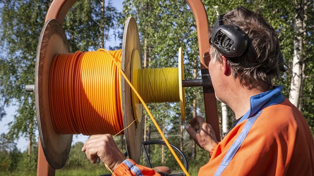 Man med arbetskläder står vid kabeltrumma med orangefärgad lina