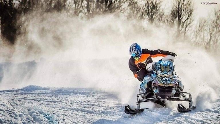 Gustav Salomonsson sitter på en skoter och kör så snön ryker