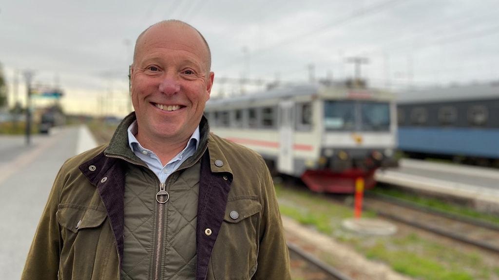 Leende man med kal hjässa står på tågstation med järnvägsspår och tåg i bakgrunden