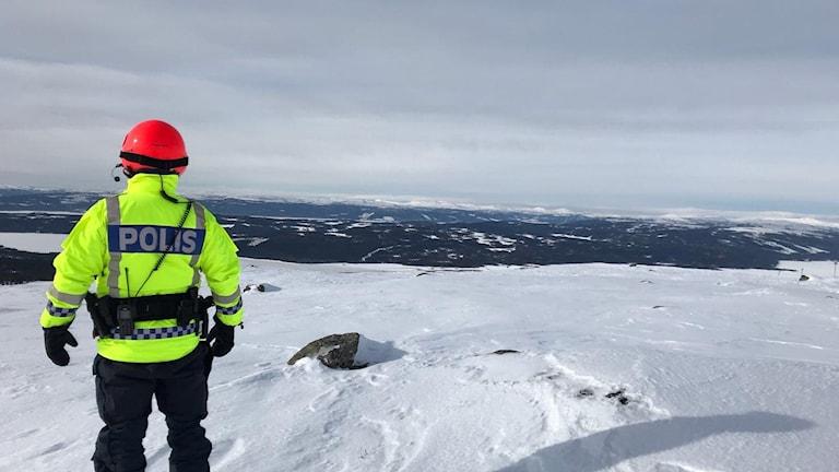 Polisman i gula kläder och röd hjälp tittar ut över ett fjäll i frosviken i norra jämtland