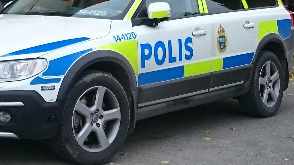 Polisbil står på asfalt