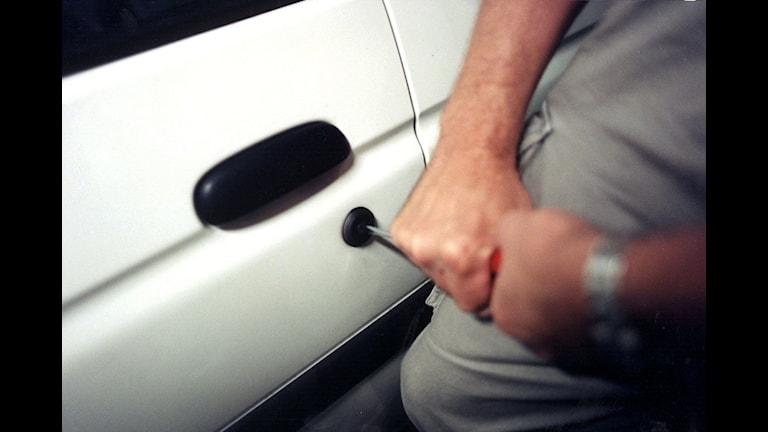 Närbild på två händer som försöker bryta upp ett billås med en skruvmejsel.