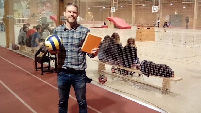 En man i skjorta står i en storhall med en boll och en bok i händerna.