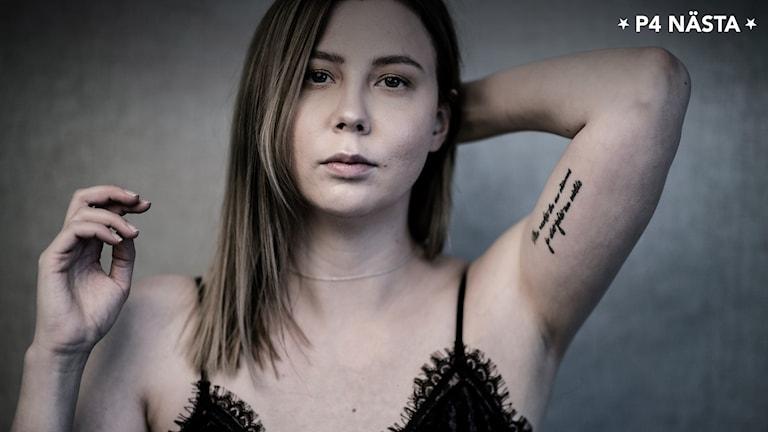 Porträttbild ung kvinna med långt, rakt mellanblont hår, iklädd svart topp med smala axelband, tatuering undersida vänster arm håller samma arm bakom nacken