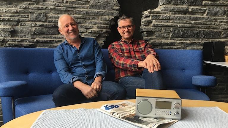 Två män sitter i en soffa, på bordet framför ligger en papperstidning och en radioapparat