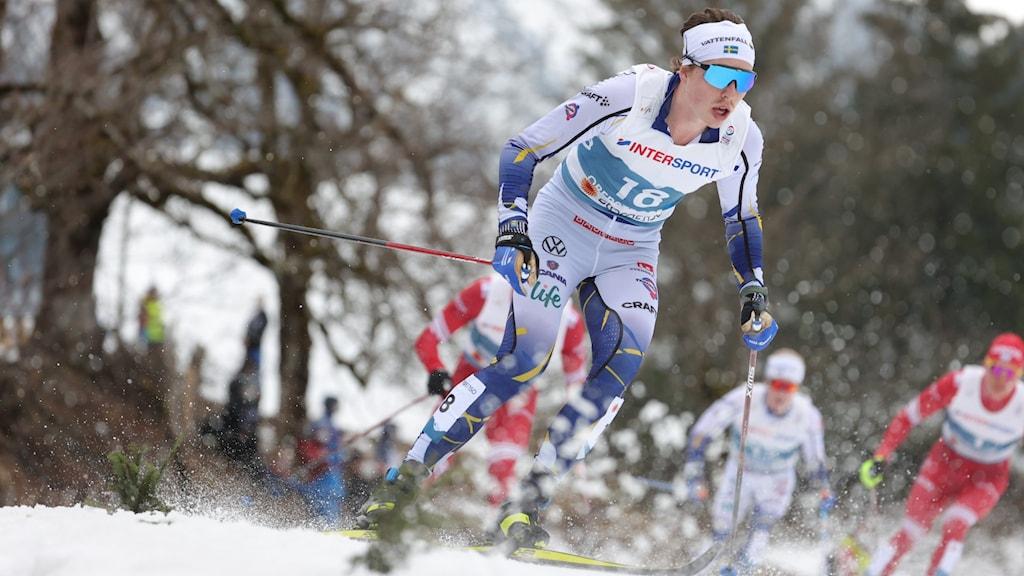 En klunga manliga längdskidåkare i spåret under tävling