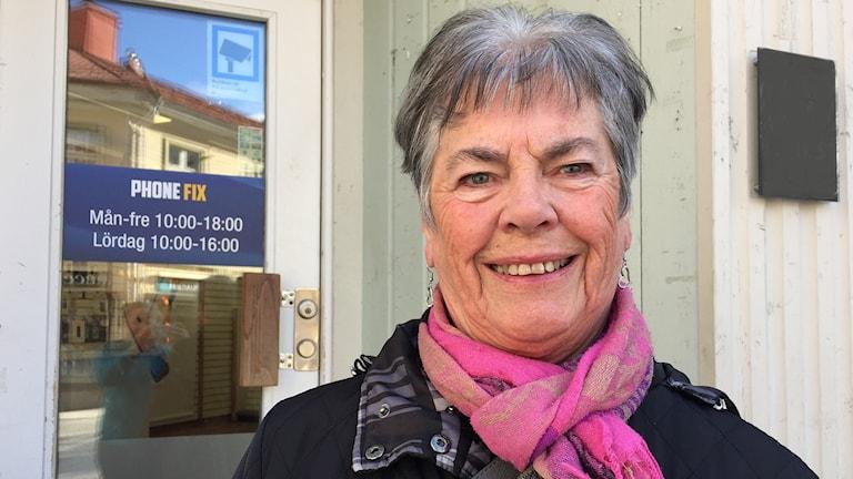 Porträttbild - äldre kvinna med kort hår står framför dörr