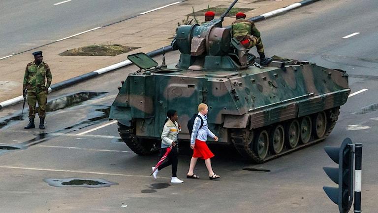 Flickor går förbi beväpnade militärer och en pansarvagn