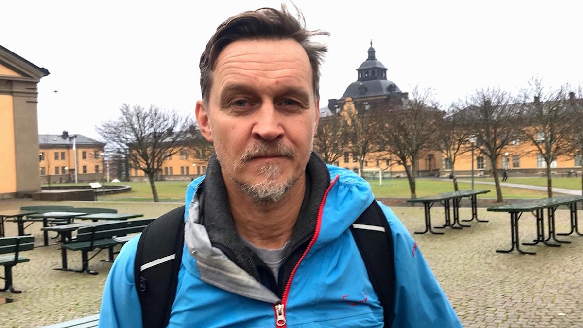 Kortklippt medelålders man med gråsprängt skägg i blå jacka och ryggsäck utomhus på campusområde med gulrappade hus