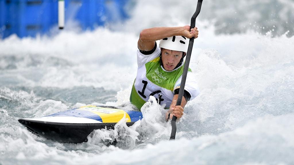 Man i kanot paddlar i forsande vatten