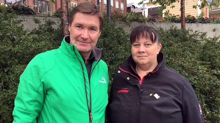 Man i grön jacka och kvinna i svarta jacka står bredvid varandra och tittar in i kameran.