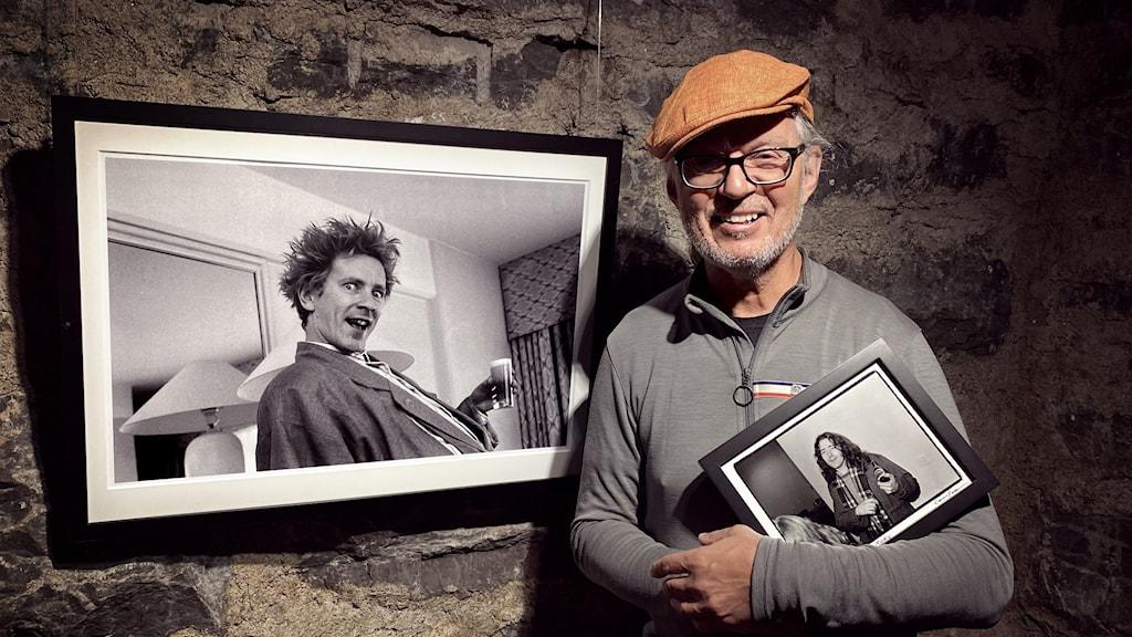Man med keps och två svartvita bilder på artister. En på väggen bakom och en i famnen.