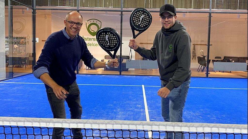En man ler in i kameran och håller i ett padelracket och bredvid honom står en annan man med svart keps och håller i padelracket.