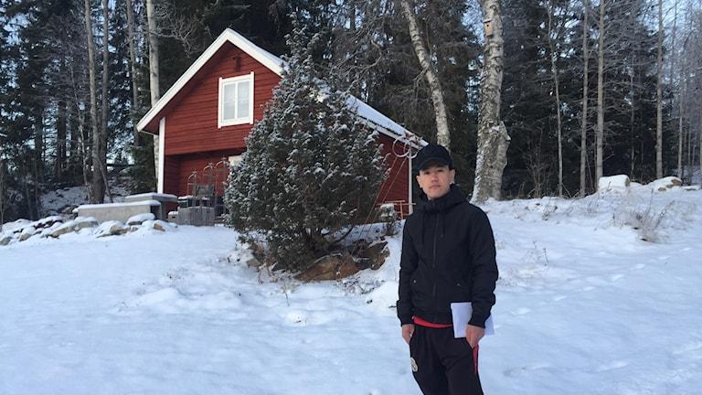 Pojke står i snö framför hus.