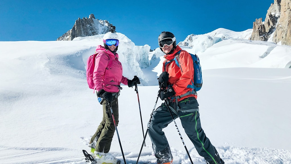 Man och kvinna i alpin skidutrustning står i solen på snöklätt fjäll