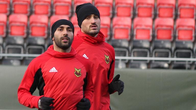 Två manliga fotbollsspelare tränar på fotbollsarena