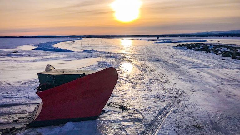 Isväg över snötäckt insjö med snöplog i förgrunern och eftermiddagssol