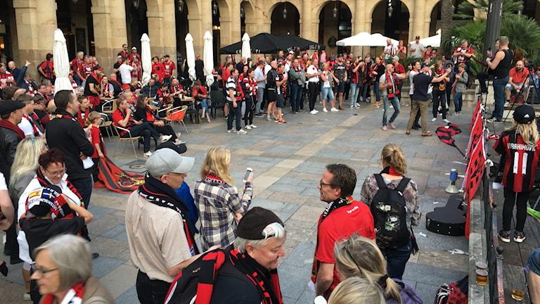 Gammalt torg fullt med folk i svartröda kläder.