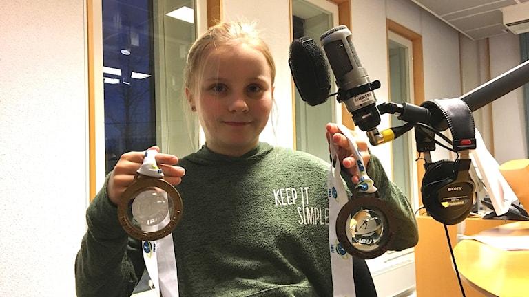 Flicka håller upp en bronsmedalj och en guldmedalj