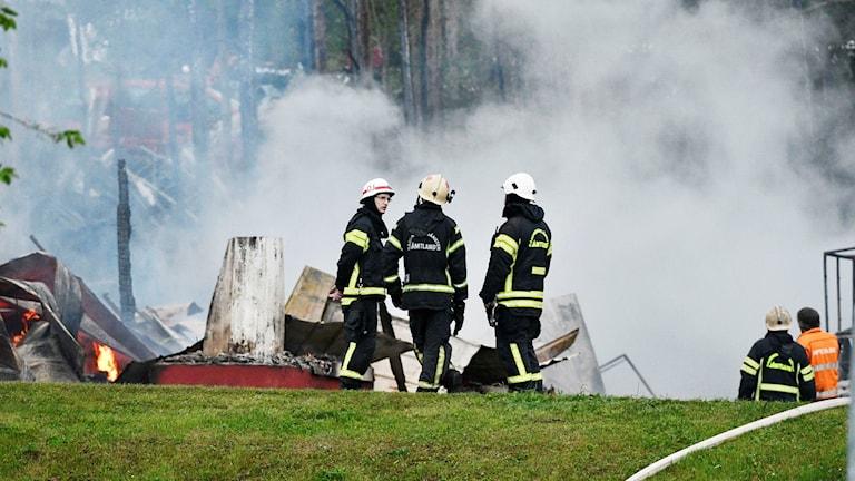 Brandmän står i rök vid nedbrunnet hus