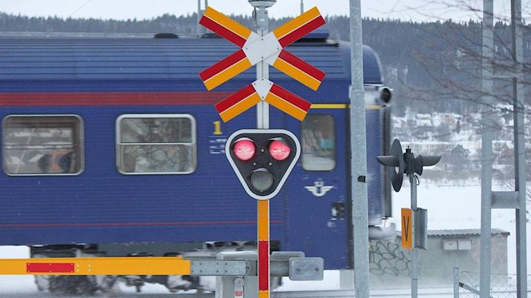 SJ-tåg passerar vid järnvägsövergång med bommarna nedfällda vintertid