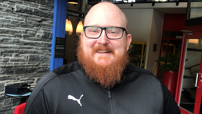 En flintskallig man med skägg ler in i kameran.