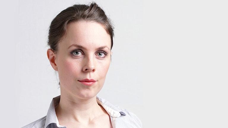 Porträttbild ung kvinna med brunt, uppsatt hår