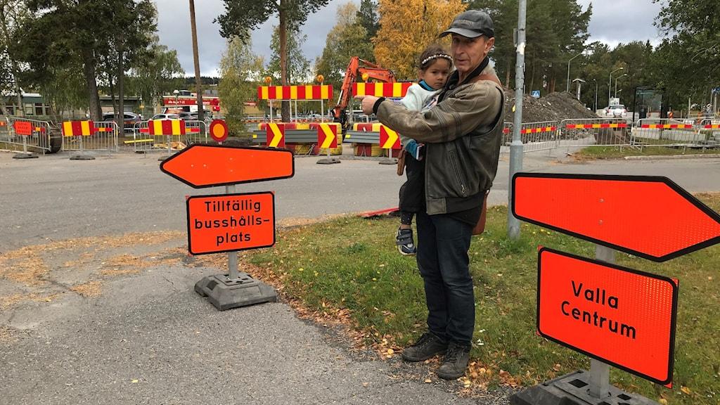 En pappa står och håller i sin dotter i famnen vid ett vägbyggde med flera vägskyltar.