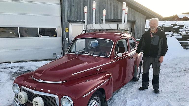 Man med vitt hår och skägg står på snön utanför en garageport bredvid en rödlackad Volvo PV som har en luciakrona på biltaket