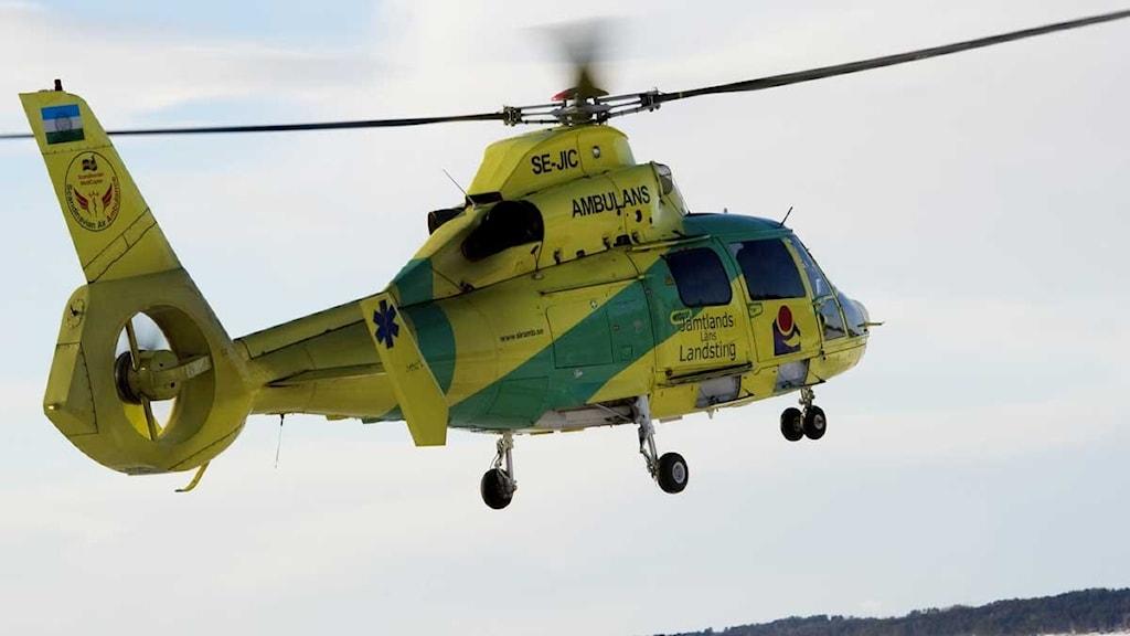 Gul ambulanshelikopter som flyger