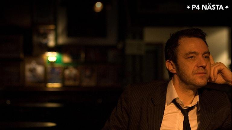 Mörkhårig man i kavaj, slips, vit skjorta sitter i tänkarposition i mörk lokal