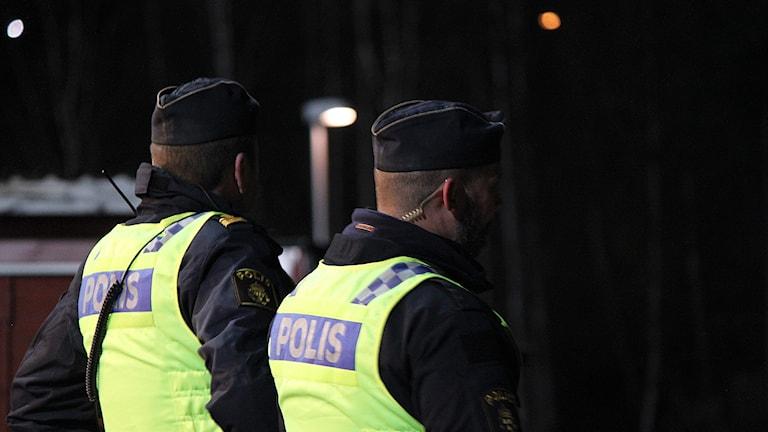 Ryggen på två polismän i reflexvästar