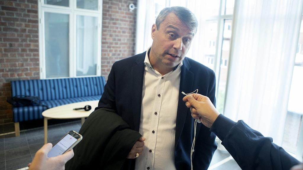 En man i svart kostym och med gråsprängt hår blir intervjuad med mikrofoner.