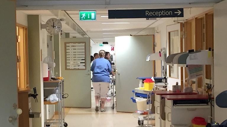 Korridorr med sjukhuspersonal som går med vagn genom koridorr.