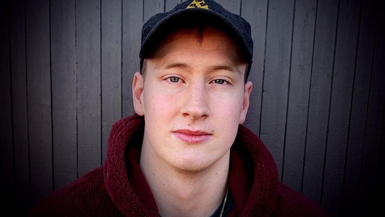 Närbild på 20-årig kille i keps framför svart vägg.